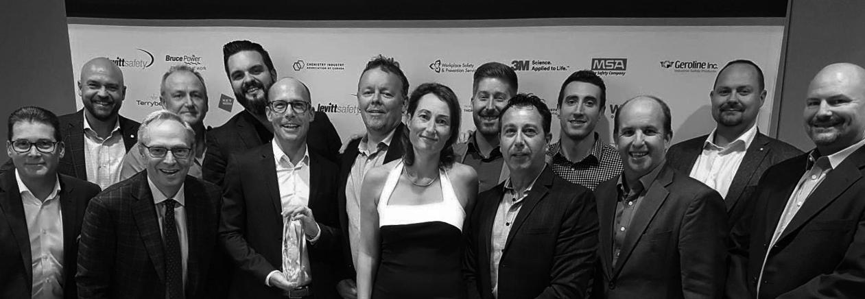 Photo of 14 Plan Group employees receiving an award